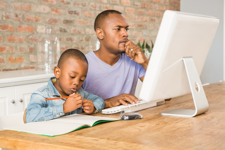 one room school house: Cute son doing his homework with father in living room