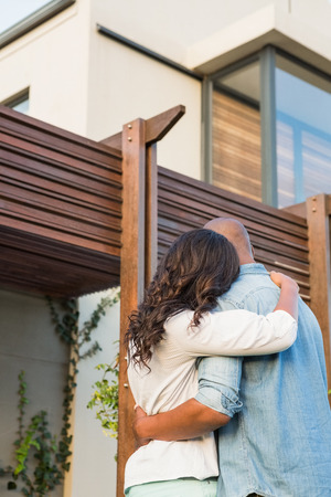 Back view of couple with arms above after buying house Stock Photo