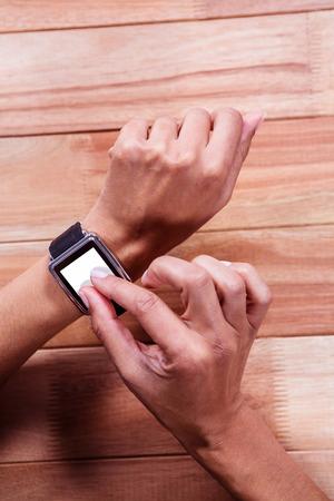 cut wrist: Woman using smart watch on wooden desk