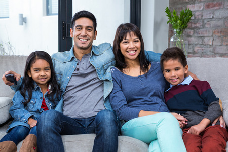 woman on couch: Happy young family watching tv in living room
