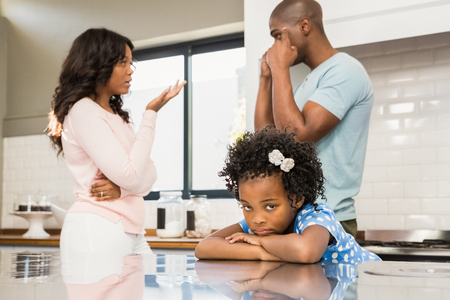 angry people: Parents arguing in front of daughter in the kitchen Stock Photo