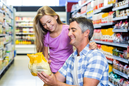 Father and daughter at the supermarket choosing product Stock Photo