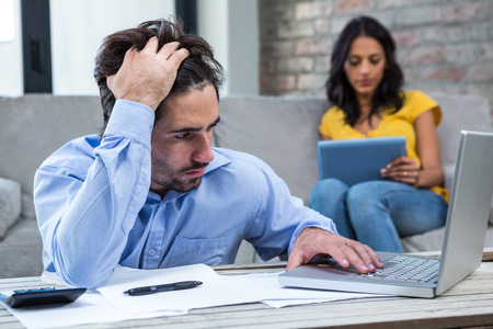 figuring: Worried man paying bills in living room while wife is on the sofa