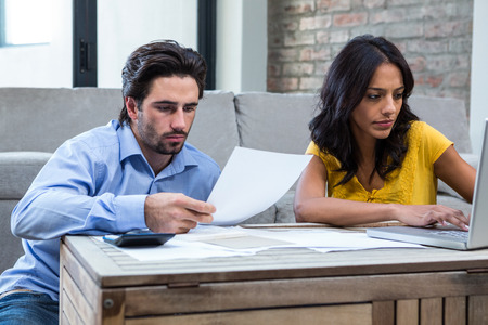 bills: Couple sitting on the floor in living room paying bills