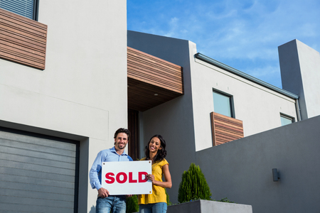 sold sign: Happy couple in front of new house with sold sign