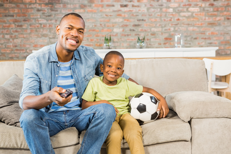 family with one child: Father and son watching tv together on the couch in living room