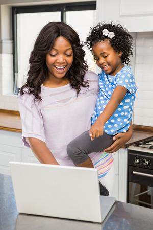 mujeres negras: Madre que usa el ordenador port�til mientras est� llevando ni�o en la cocina Foto de archivo