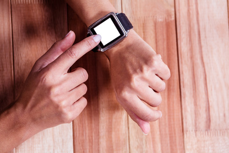 portable information device: Part of hands typing on a watch on wooden desk Stock Photo