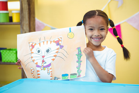 Smiling girl with a painting of her cat at the desk Stok Fotoğraf