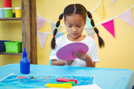 Focused girl cutting a paper plate with scissors Stock Photo