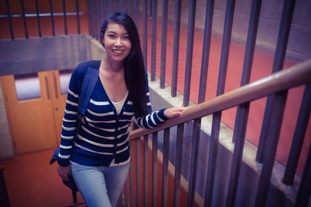 mujer bonita: Smiling student walking up steps at the university