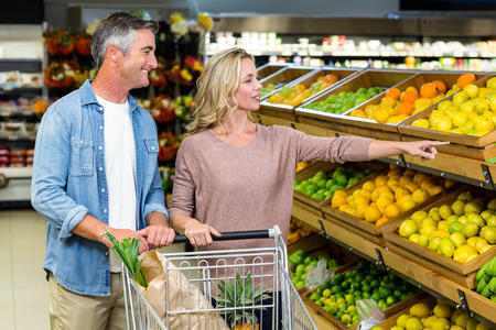 buying: Smiling couple buying food products in supermarket Stock Photo