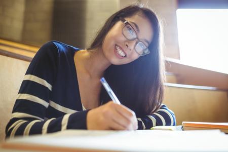 persona escribiendo: escritura de los estudiantes sonriente en el bloc de notas en la universidad Foto de archivo
