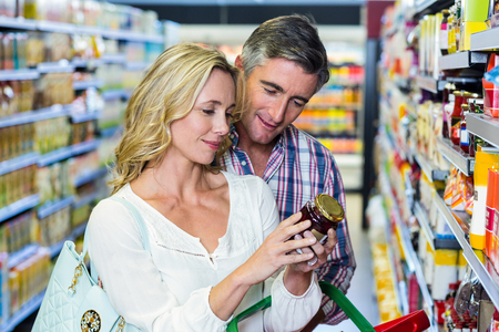 food products: Couple reading nutritional values of food at supermarket
