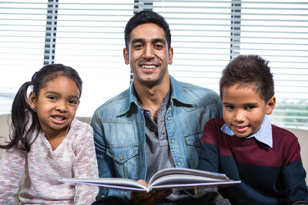 convivial: Happy father reading a book for his children in living room Stock Photo