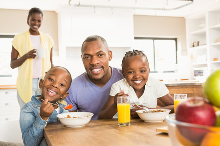 sitting at table: Casual happy family having breakfast in the kitchen