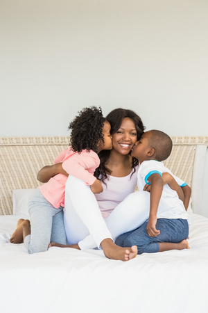 mom kiss son: Children kissing mother on bed at home Stock Photo