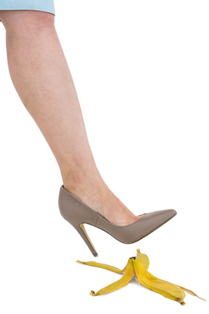 banana skin: Cropped image of businesswoman crushing banana skin against white background