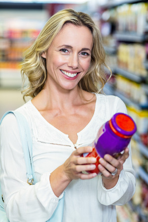 food products: Woman reading nutritional values at supermarket