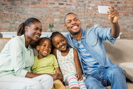 Happy family taking a selfie on the couch in living room Archivio Fotografico