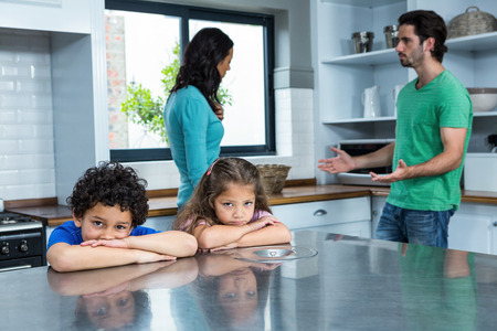 two woman: Sad children listening to parents argument in the kitchen Stock Photo