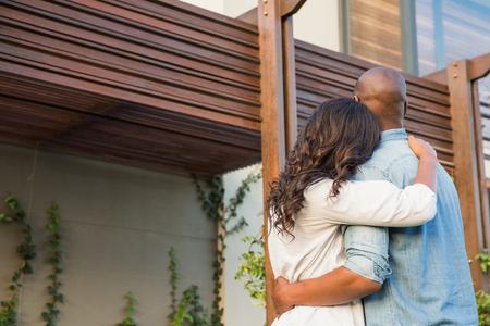 pareja en casa: Vista posterior de la pareja con los brazos por encima de la casa después de comprar Foto de archivo