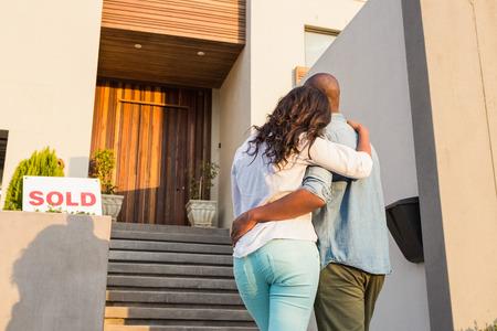 上の家を購入した後の腕とカップルの背面図 写真素材