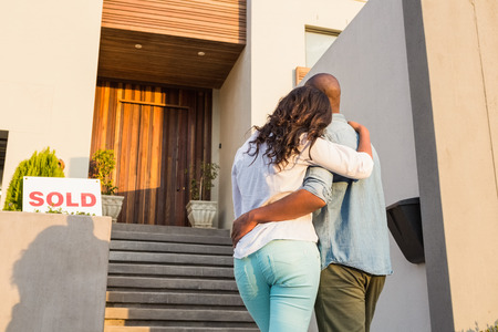 buying a house: Back view of couple with arms above after buying house Stock Photo
