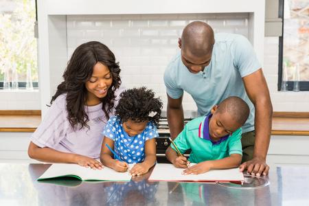 ni�os ayudando: Padres que ayudan a los ni�os que hacen la preparaci�n en la cocina Foto de archivo