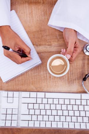 prescription pad: Doctor holding pen and hot beverage on desk