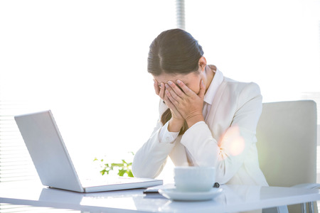 covering face: Worried businesswoman covering face at the desk in work