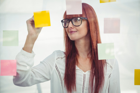lady in red: Attractive hipster woman writing on sticky notes in her office
