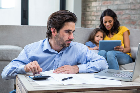 one people: Serious man paying bills in living room while wife and daughter are on the sofa Stock Photo
