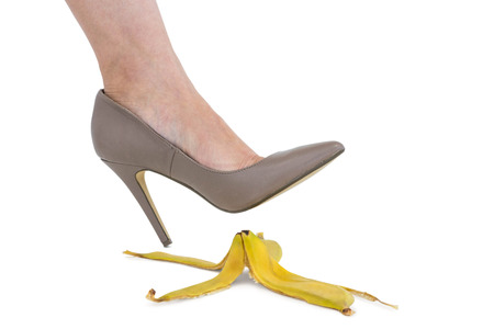 banana skin: Cropped image of businesswoman crushing banana skin against white background