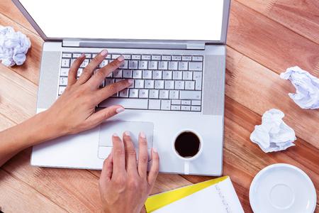 wooden desk: Part of hands typing on laptop on wooden desk Stockfoto
