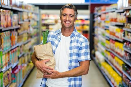 grocery bag: Smiling man holding grocery bag in supermarket