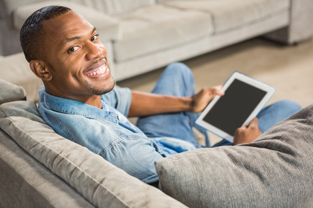 over the shoulder view: Over shoulder view of casual man using tablet in living room