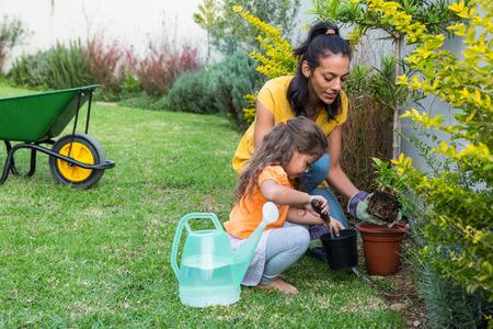 Sourire mère et la fille jardinage ensemble