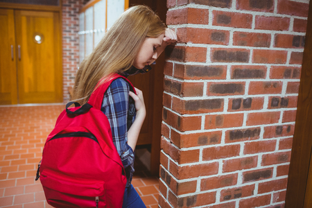 school teens: Worried student leaning against the wall at the university