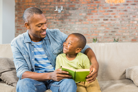 Father and son reading on the couch in living room Foto de archivo