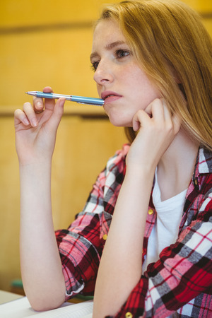 unsure: Unsure student holding pen during class at the university