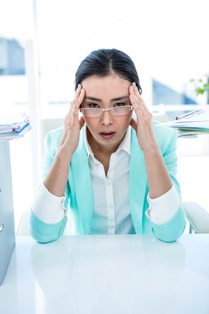 out of business: Stressed out business woman at the desk in work