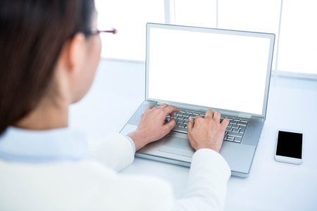 Rear view of businesswoman using laptop at the desk in work