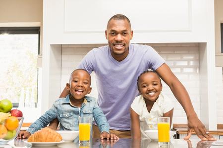 Casual familia feliz desayunando en la cocina