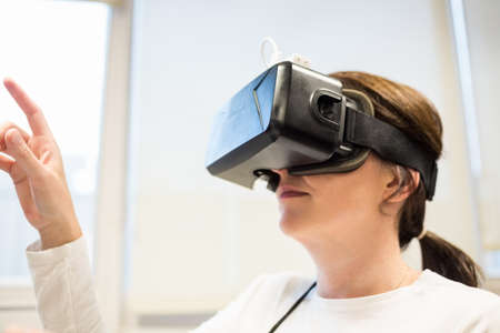 headset business: Businesswoman using oculus rift headset in the office LANG_EVOIMAGES