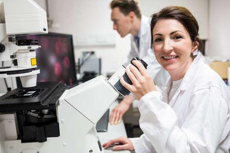 microscopio: Científico que mira a través de un microscopio en el laboratorio