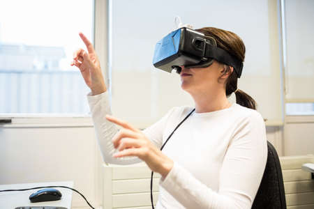 rift: Businesswoman using oculus rift headset in the office LANG_EVOIMAGES