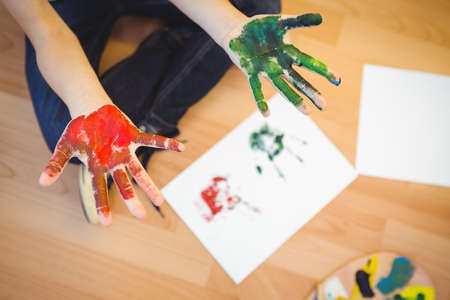 hands off: Boy showing his green and red painted hands off the paper