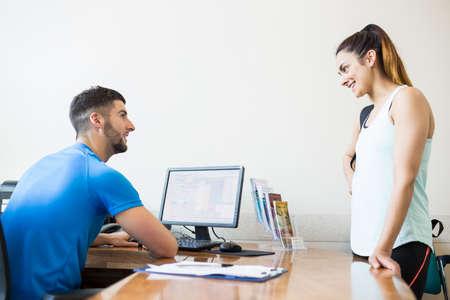 recepcion: Athletic mujer hablando con el entrenador de fitness en el gimnasio LANG_EVOIMAGES