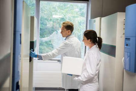 biochemist: Two scientists using large fridge unit in the lab LANG_EVOIMAGES